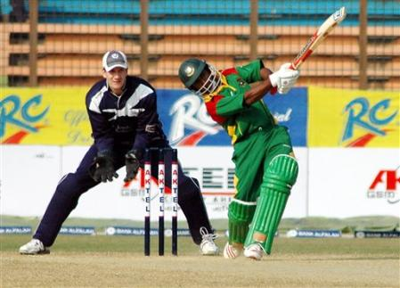 Bangladeshi batsman Aftab Ahmed, scores his fifty as Scotland keeper Colin Smith looks on during the first limited over international cricket match against Bangladesh at Chittagong Divisional Stadium.