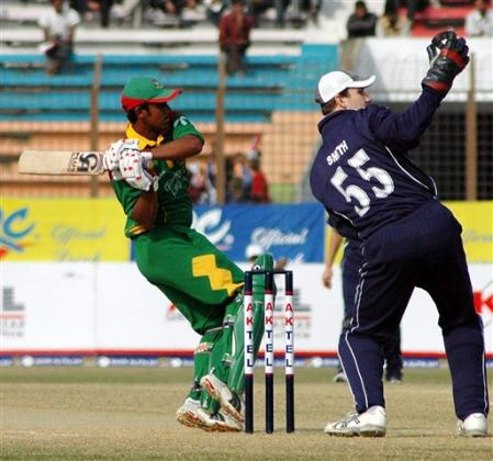 Bangladeshi batsman Shahriar Nafees, plays a shot as Scotland wicket keeper Colin Smith looks on during the first limited over international cricket match against Bangladesh at Chittagong Divisional Stadium